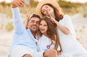Image of young cute happy family having fun together outdoors at the beach make selfie by mobile pho poster