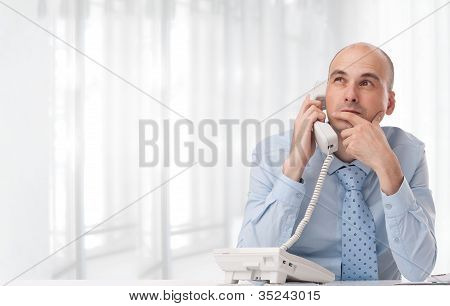 Businessman Talking On Landline Phone At Office