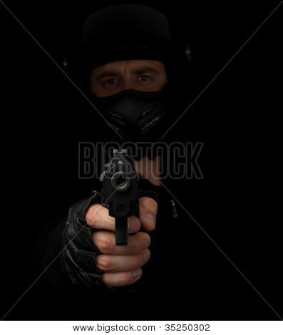 Armed Assassin With Motorcycle Helmet Aiming Into The Camera