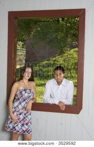 Teenage Couple Standing In Red Window