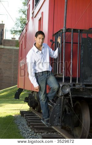 Teenage Boy Standing On Red Caboose