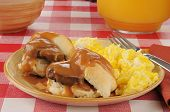 foto of biscuits gravy  - A plate of sausage and biscuits with scrambled eggs and orange juice - JPG