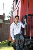 stock photo of caboose  - Teenage boy standing on the steps of a red caboose - JPG