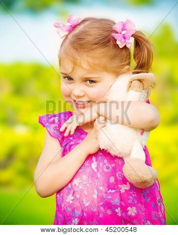 Closeup portrait of cute baby girl hugging soft toy outdoors, having fun on backyard in daycare, spring season, happiness concept