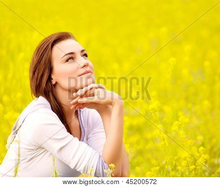Closeup portrait of attractive brunette female sitting down on yellow floral field, rapeseed plantation, summer vacation concept