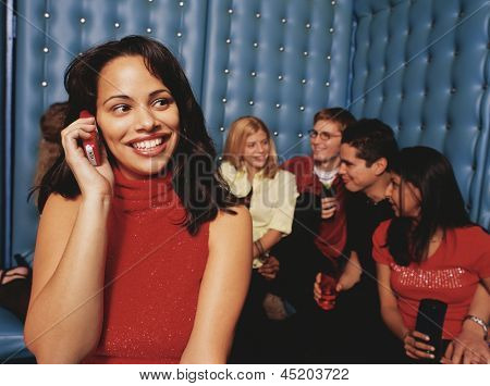 Young woman taking phone call in night club