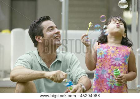 Father and daughter blowing bubbles