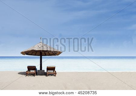 Beach chair and umbrella on white sand beach