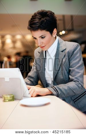 Young woman working on  tablet in cafe