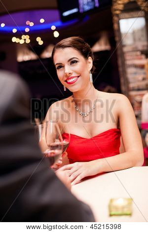 Beautiful young woman in red dress in restaurant