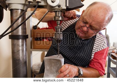 senior metal worker using industrial drilling machine in workshop