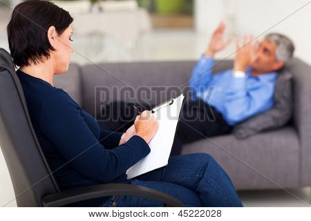 middle aged female psychologist making note while patient talking