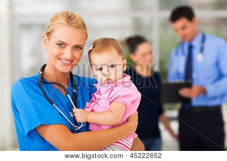 beautiful female nurse holding baby girl in hospital