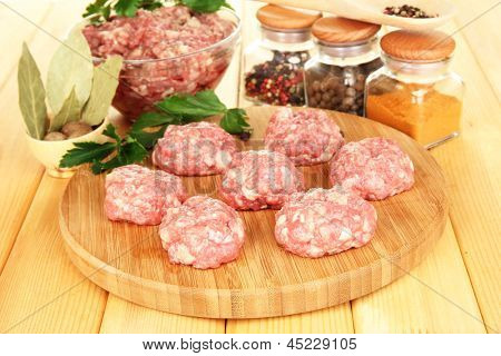 Raw meatballs with spices on wooden table