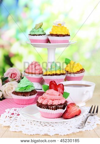 Beautiful cupcakes on dining table on natural background