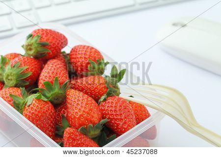 Healthy lunch with strawberry and blueberry mix in office
