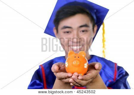 Portrait of Asian graduate student with piggy bank