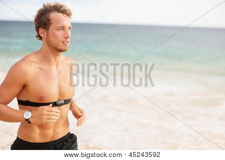 Runner man running with heart rate monitor on beach topless. Fit Fitness athlete model jogging training for marathon run outside. Young male caucasian in his twenties