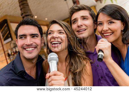Group of people karaoke singing at the bar having fun