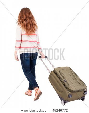 back view walking woman with suitcase. beautiful redhead girl in motion. backside view of person. Rear view people collection. Isolated over white background. Red-haired beauty rolls for  carry-on bag
