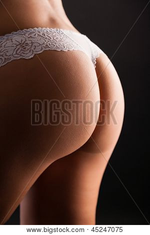 Woman's backside in lingerie on black background