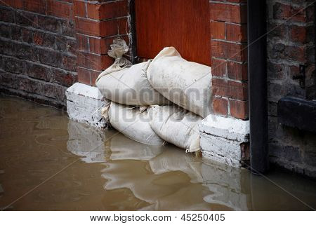 Sandbag barrier in doorway of flooded street in York.