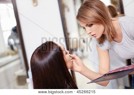 Visagiste make-up girl in a beauty salon