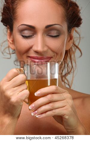Beautiful middleaged woman in towel with herbal tea