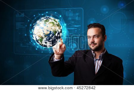 Handsome young businessman touching high-tech 3d earth panel, elements of this image furnished by NASA