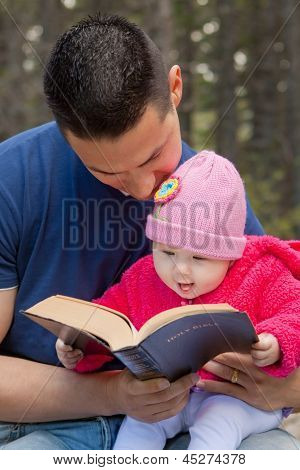Dad And Baby Daughter Reading Bible