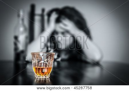 Alcohol addiction : Portrait of a lonely and desperate drunk hispanic woman (image focused on her drink)