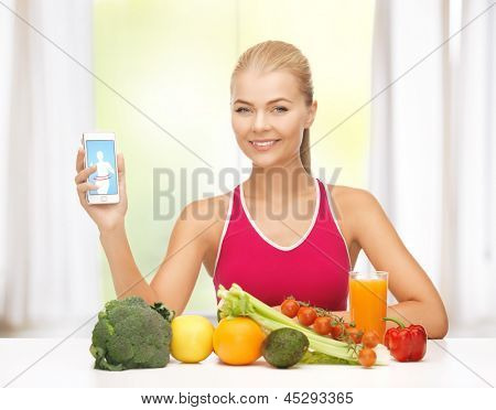 woman with fruits and vegetables counting calories in smartphone