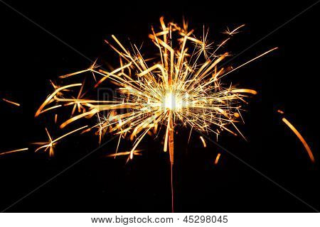 burning christmas sparkler isolated on blue background