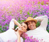 Beautiful happy couple lying down on purple lavender field, having fun on floral glade, summer natur