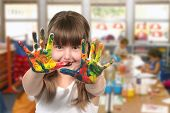 stock photo of kindergarten  - Happy Girl Painting With Her Hands in Kindergarten Class - JPG