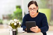 beautiful modern mature woman using tablet computer