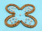 pic of talisman  - concept of four leaf clover made of rusty retro horse shoes and six number gamble dices on blue background - JPG
