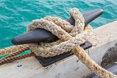 foto of bollard  - Mooring Bollard with rope on pier by the sea - JPG