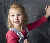 portrait of little cute girl near blackboard