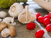image of crimini mushroom  - Garlic with cherry tomatoes crimini mushrooms and an artichoke by kitchen window - JPG