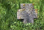 stock photo of macedonia  - Exalted old stone cross in Macedonia cemetery in spring - JPG