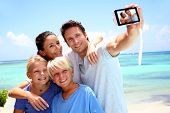 image of children beach  - Couple and children taking family picture - JPG