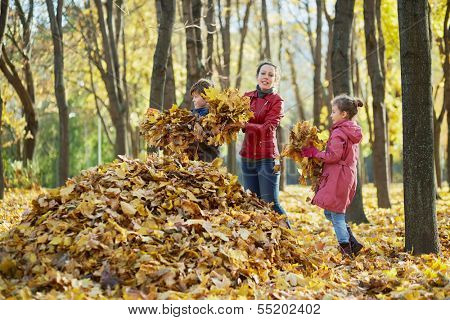Mother and her two children gather fallen leaves in one big heap in autumn park