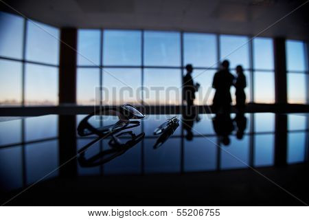 Close-up of eyeglasses and pen at workplace on background of office workers interacting