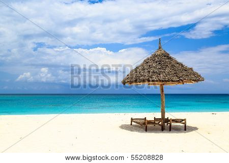 Beds And Umbrella On A White Sand Beach