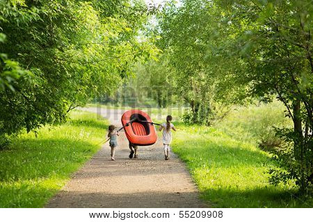 Three children carry a rubber boat with oars on a footpath in the forest