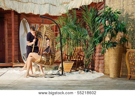 Young man stands near hanging chair with woman and looks at her next to beach house.