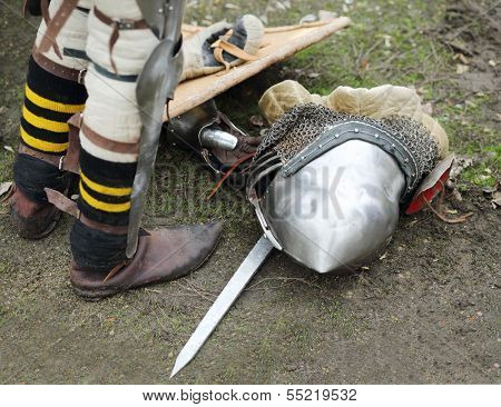 Legs of man and armored metal medieval helmet on ground outdoor.