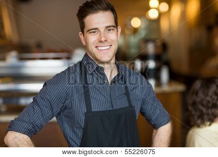 Portrait of happy young male owner standing in cafe
