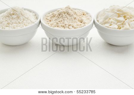 coconut flour and flakes in three white ceramic bowls on white table cloth